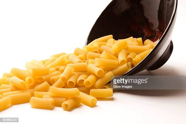 Close-up of a spilled bowl of raw rigatoni pasta