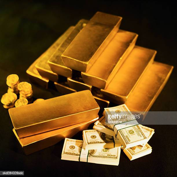 Close-up of a stack of gold bars and one hundred dollar bills and one euro coins