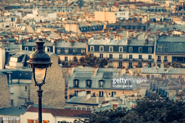 Close-up of a street lamp with the blurry background of Paris city in the morning