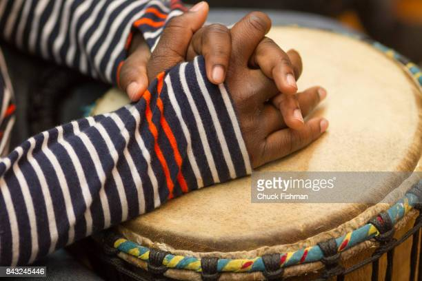 Closeup of a student's clasped hands on a djembe during a drum circle workshop Rockland County New York June 9 2016
