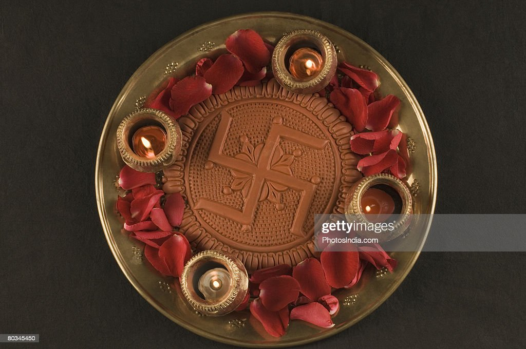 Close-up of a swastika with burning oil lamps in a plate : Stock-Foto