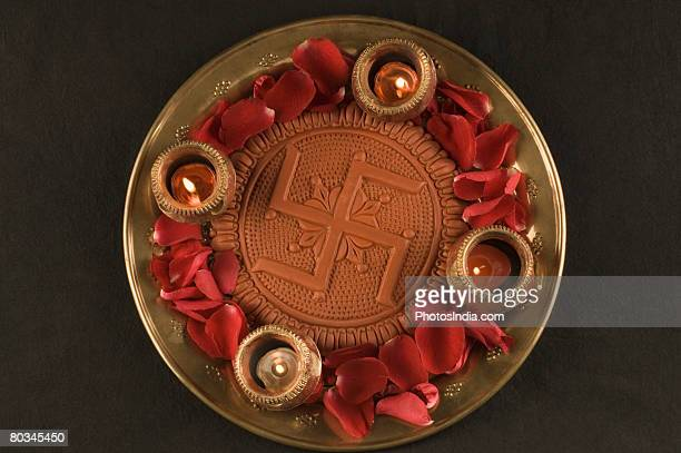 Close-up of a swastika with burning oil lamps in a plate