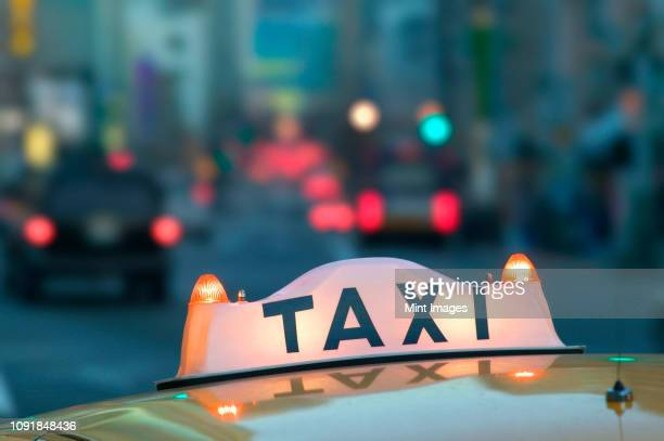 closeup of a taxi sign on top of a taxi cab in the city at night. - yellow taxi stock pictures, royalty-free photos & images