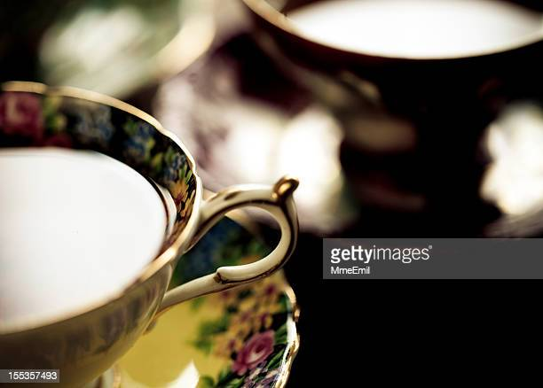 A closeup of a tea cup and saucer with gold trim