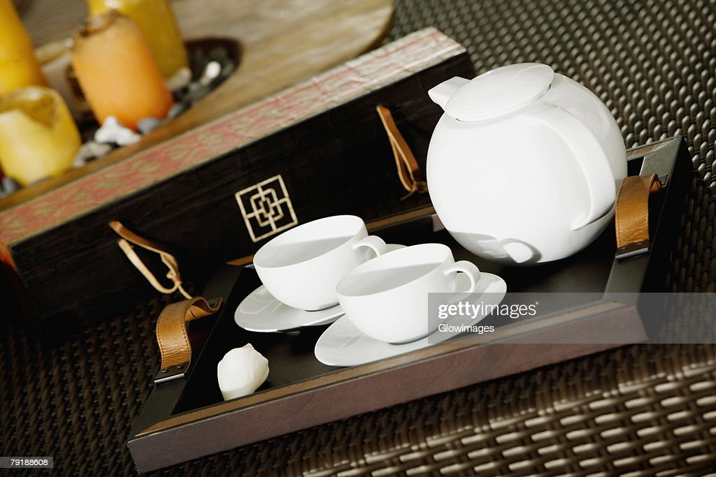 Close-up of a teapot with teacups on a serving tray : Stock Photo