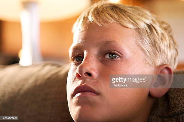 close-up of a teen boy's face as he looks off into the distance - thinkstock foto e immagini stock