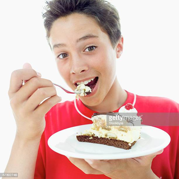 Close-up of a teenage boy (15-17) eating a slice of chocolate cake with a fork