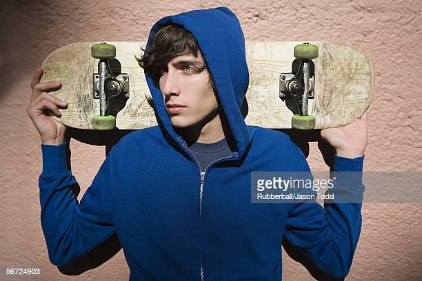 Close-up of a teenage boy holding a skateboard