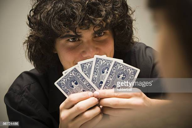Close-up of a teenage boy holding cards