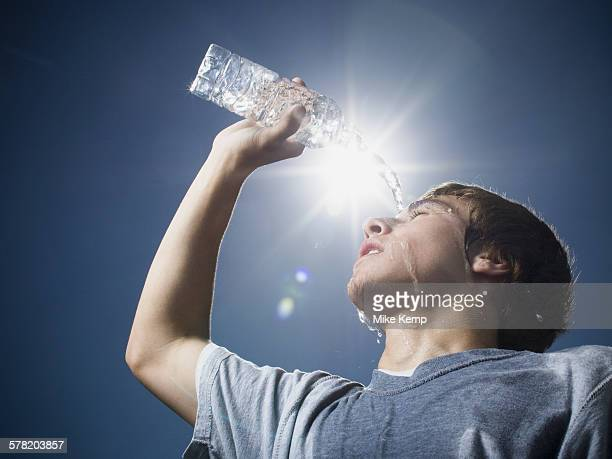 Close-up of a teenage boy pouring water over his head