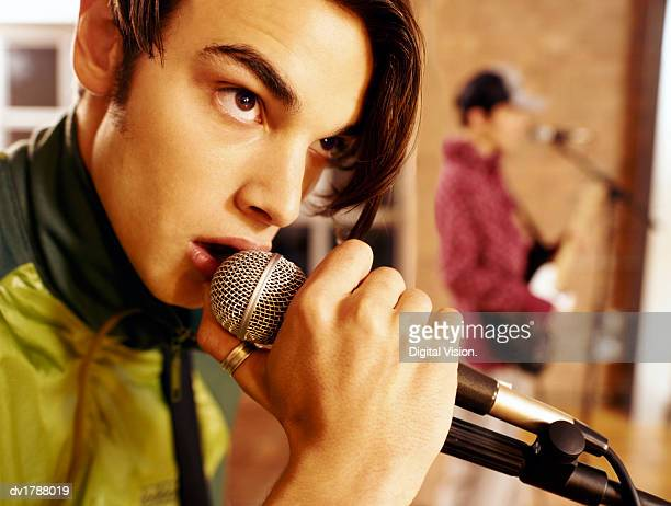 Close-Up of a Teenage Boy Singing Into a Microphone