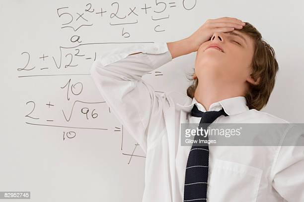 Close-up of a teenage boy standing in front of a whiteboard and looking stressed