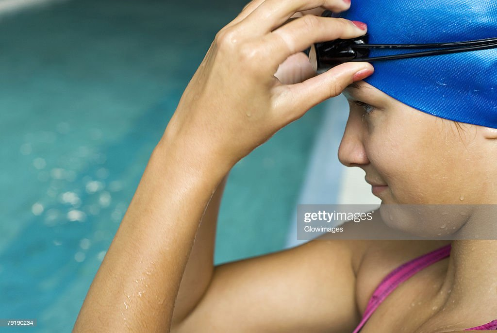 Close-up of a teenage girl adjusting her swimming goggles : Foto de stock