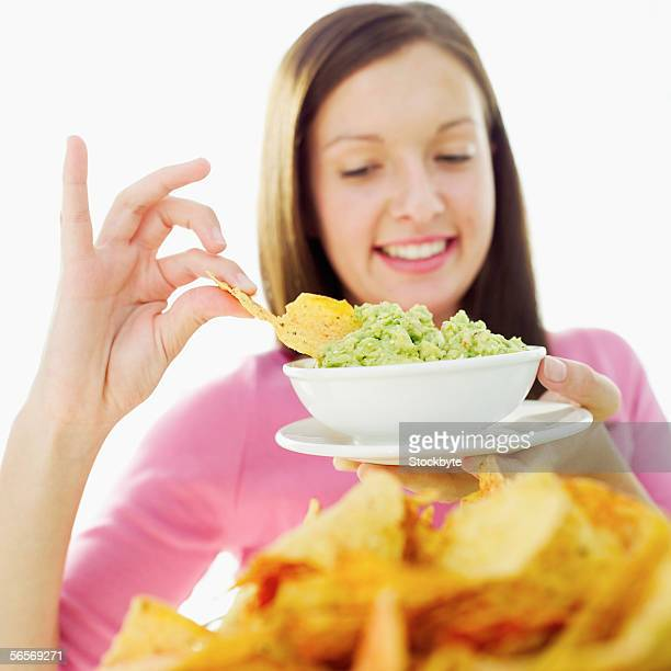 close-up of a teenage girl dipping a nacho into dip - guacamole stock photos and pictures