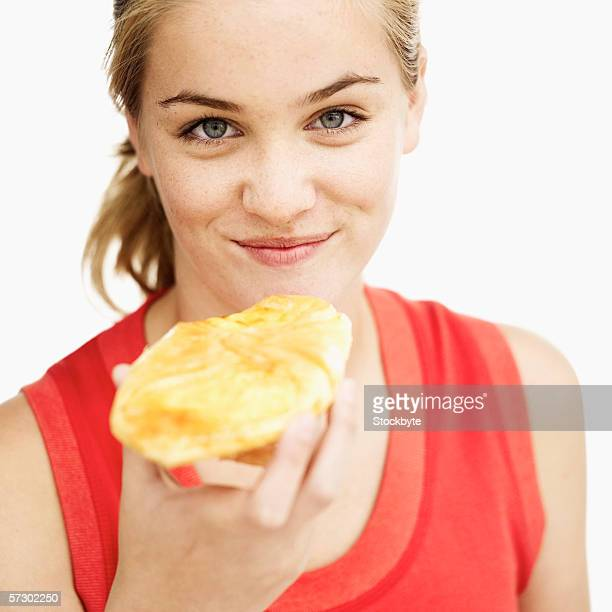 Close-up of a teenage girl (15-17) holding a Danish in her hand