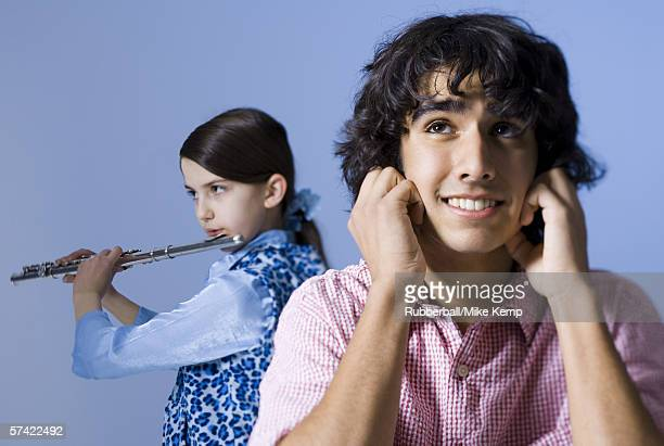 close-up of a teenage girl playing the flute behind a teenage boy - fingers in ears stock pictures, royalty-free photos & images