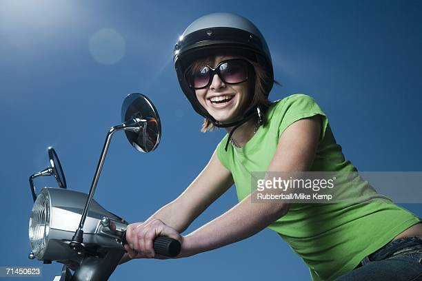 Close-up of a teenage girl riding a scooter