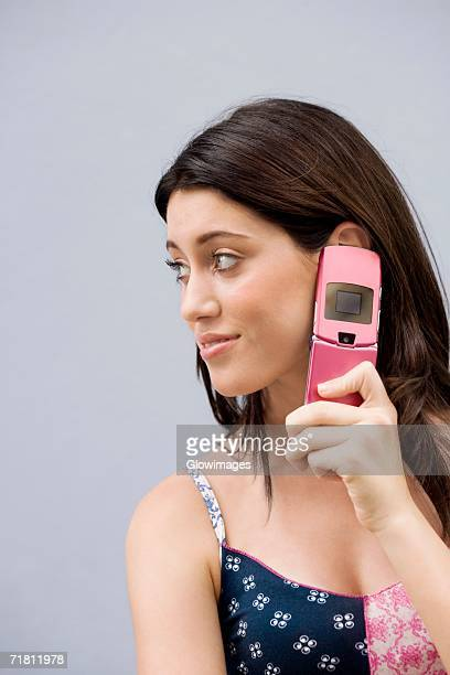 Close-up of a teenage girl using a mobile phone and smiling