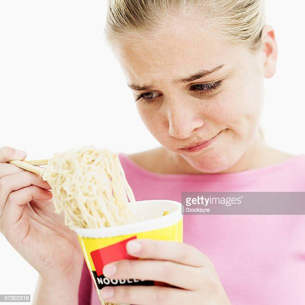 Close-up of a teenage girl (15-17) using chopsticks in a cup of instant noodles