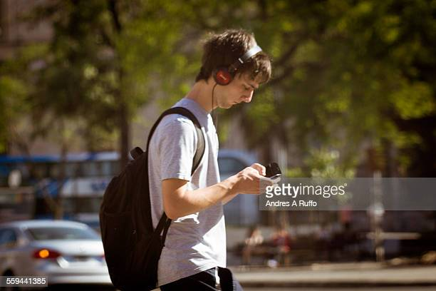 Closeup of a teenage person walking and looking at a mobile phone in hand and listening to music in the city of Cordoba in Argentina pm on November 9...