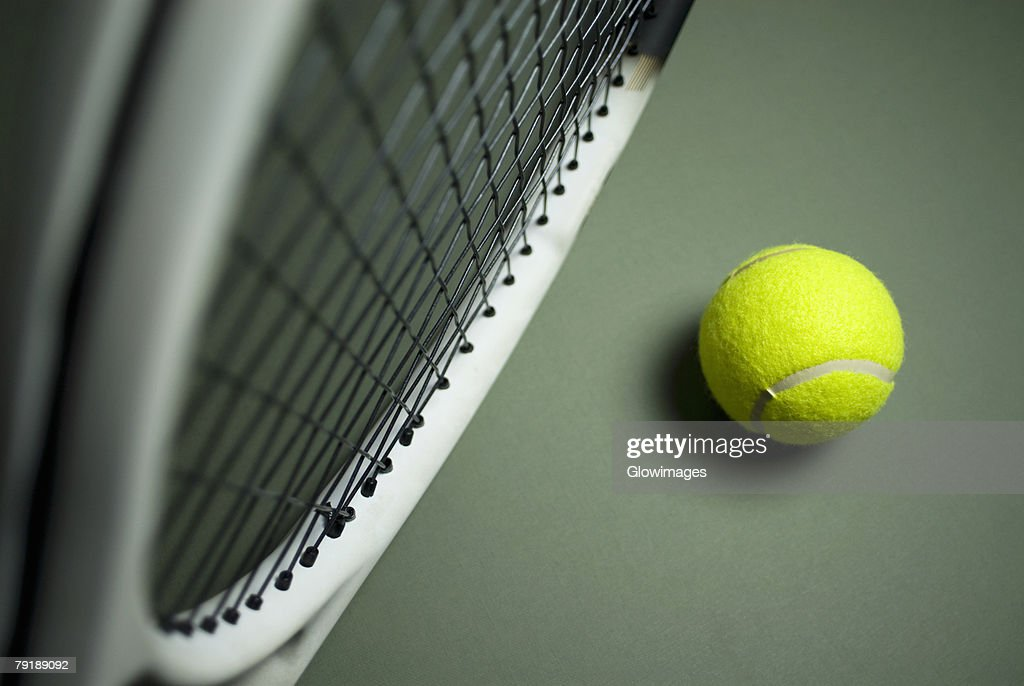 Close-up of a tennis racket with a tennis ball : Stock Photo
