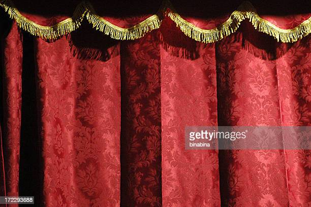 Close-up of a theater's red curtain with gold accents