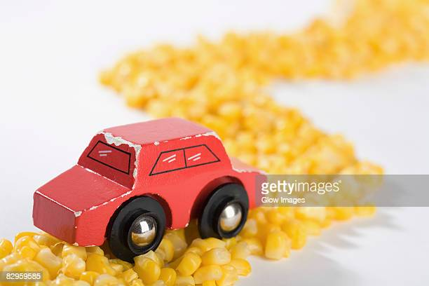 Close-up of a toy car on a road made up of corns