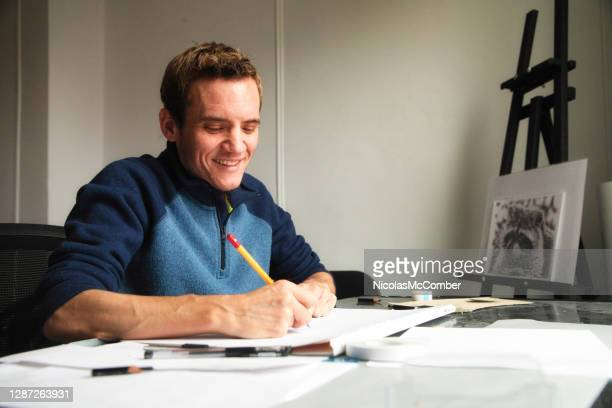 close-up of a trans male artist smiling as he draws at his workshop table - autism stock pictures, royalty-free photos & images