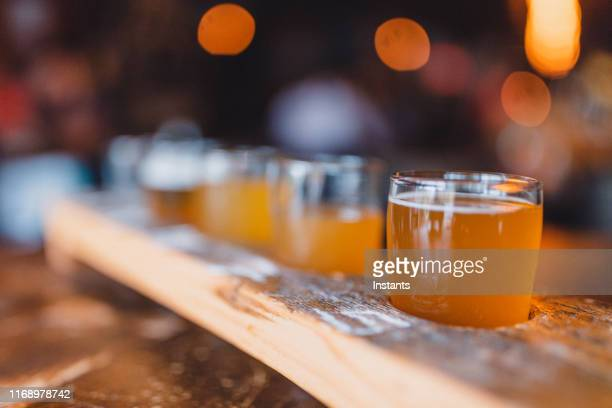 close-up of a variety of beers set on a beer flight. - help:ipa stock pictures, royalty-free photos & images