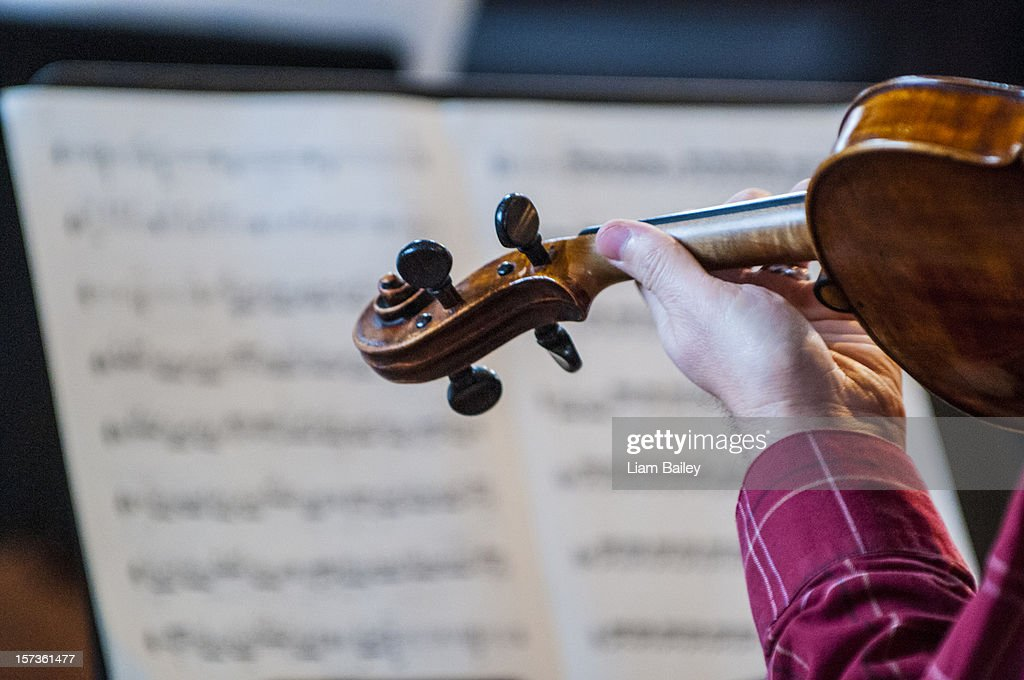 Close-up of a violin, a violinist's hand and music : Stock Photo
