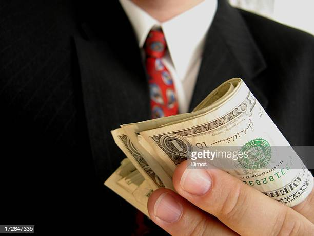 Close-up of a wad of money being held by a businessman