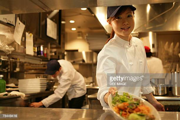 Close-up of a waitress holding a plate of food