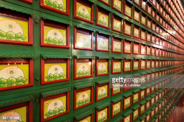 close-up of a wall full of drawers that contain ashes of the deceased inside the man mo temple in sheung wan on the hong kong island in hong kong, china. - man motempel stockfoto's en -beelden