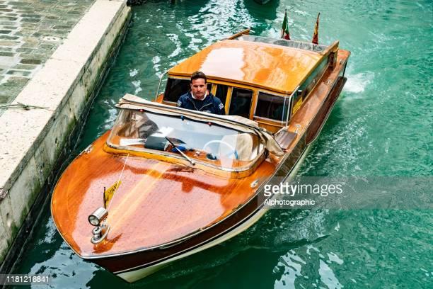 nahaufnahme eines wassertaxis auf einem kanal in venedig - vaporetto stock-fotos und bilder