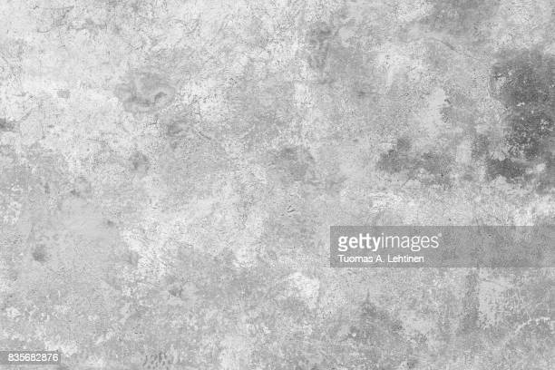 Close-up of a weathered and aged concrete wall, paint partly peeled off. Texture background in black and white.