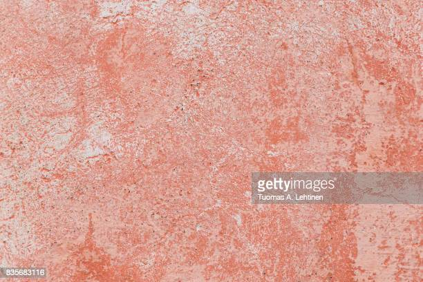 Close-up of a weathered and aged concrete wall with bleached red paint. Texture background.