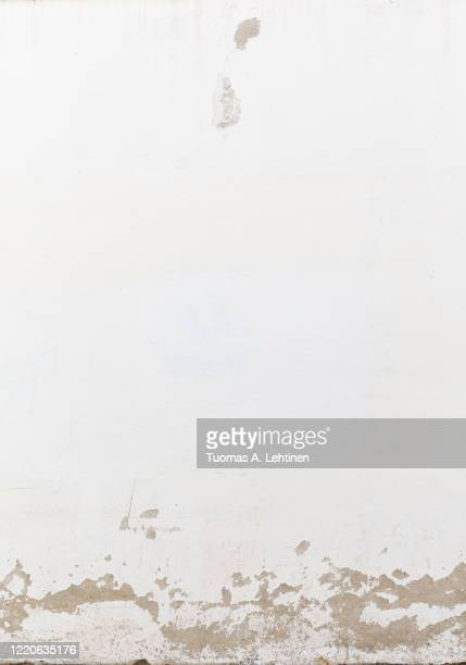 close-up of a weathered and old concrete wall, white paint has partly peeled off. - deterioration stock pictures, royalty-free photos & images