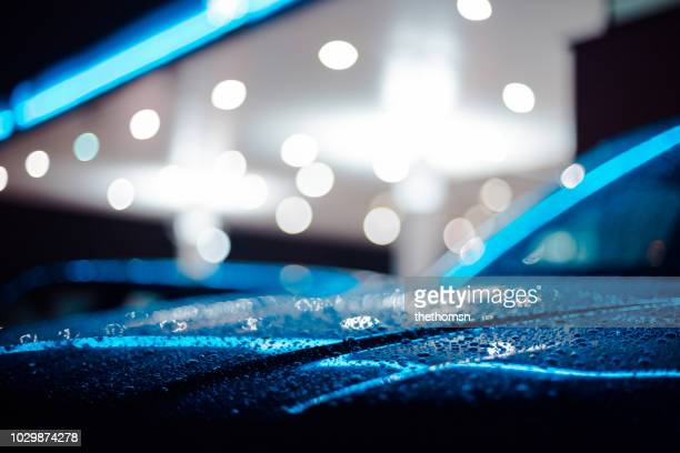 close-up of a wet car at a petrol station during night, germany - spiegelung stock-fotos und bilder
