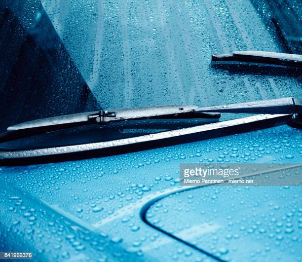 Close-up of a wet windshield and dashboard of a blue car at night