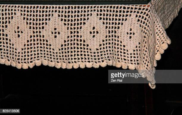 Close-up of a white crochet tablecloth against black background