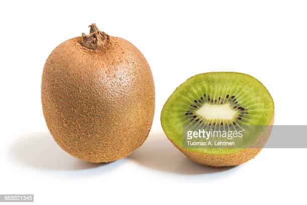 closeup of a whole and half kiwifruits with shadow - bisected stock pictures, royalty-free photos & images