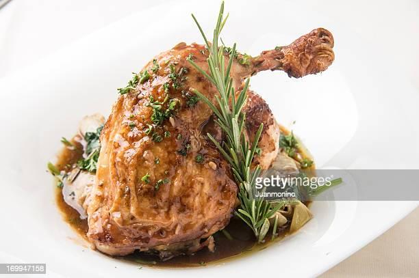Gros plan d'un ensemble de romarin poulet grillé sur plaque blanche.