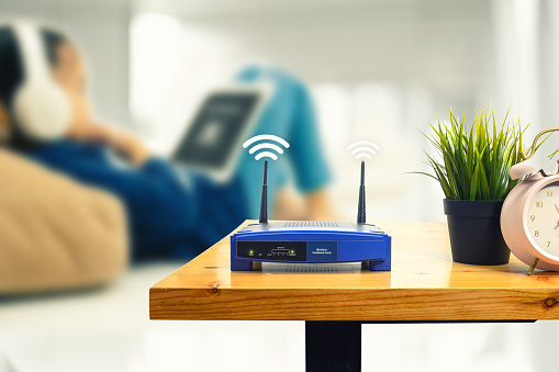 closeup of a wireless router and a man using smartphone on living room at home ofiice 1131810871