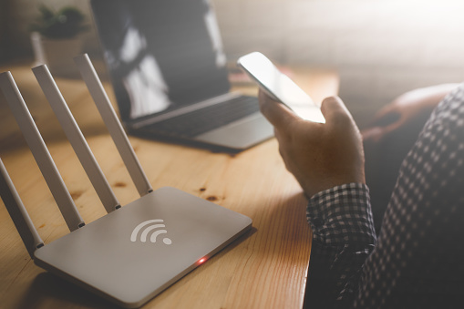 closeup of a wireless router and a man using smartphone on living room at home ofiice 915347404
