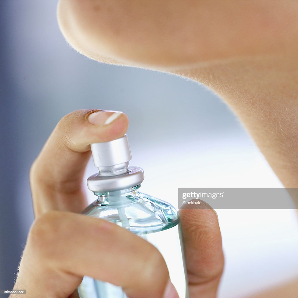 close-up of a woman about to spray perfume on her neck : Stock Photo