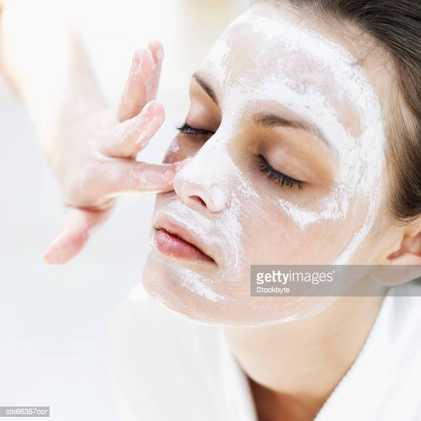 close-up of a woman applying face pack - beauty care occupation stock photos and pictures