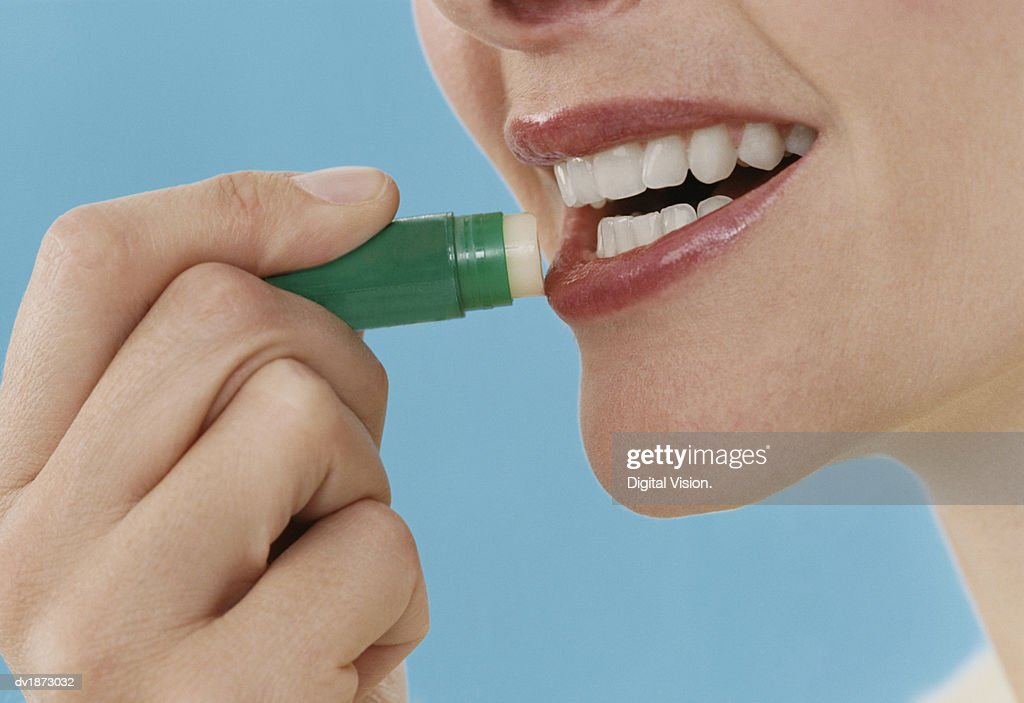 Close-Up of a Woman Applying Lip Balm : Stock Photo