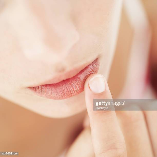 close-up of a woman applying lip balm - lip balm stock pictures, royalty-free photos & images