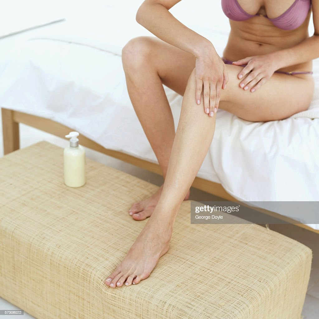 Close-up of a woman applying lotion on her leg sitting on a bed in underwear : Stock Photo