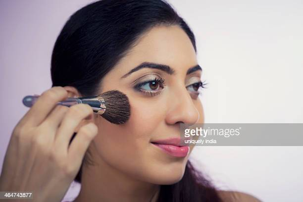 Close-up of a woman applying make-up on her face with a make-up brush